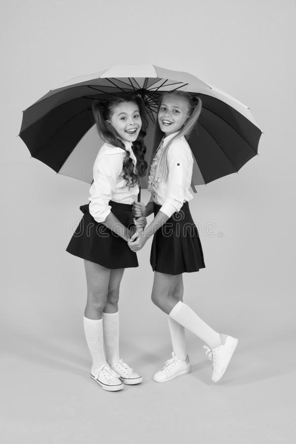 Place for both of us. Fashion accessory. Girls friends with umbrella. Rainy day. Happy childhood. School time. Rainbow. Umbrella. Colorful life. Schoolgirls stock photo