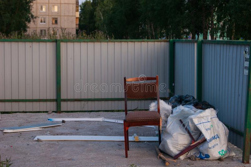 A place for collecting garbage in the yard of several multi-storey buildings. Editorial photo. Someone threw out a chair royalty free stock images