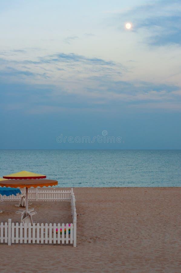 Place de la barrière en bois blanche sur le sable de plage avec le fond sombre de paysage marin d'été photos libres de droits