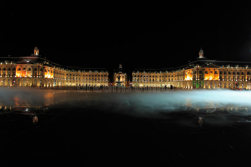 Place de la Bourse with smoke and water mirror. Place de la Bourse (1745-1747, designed by Jacques-Ange Gabriel) and water mirror at night, Bordeaux, France royalty free stock image