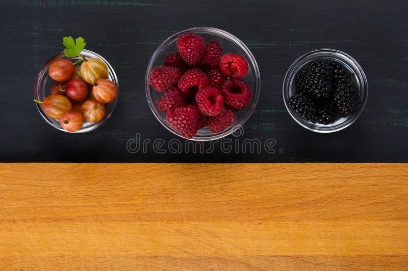 A place for inscription on a wooden surface, with three plates of black background with berries of raspberries, gooseberries, blac royalty free stock image