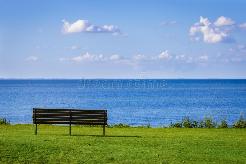 A lonely bench in front of the sea during a clear summer day in Denmark royalty free stock images