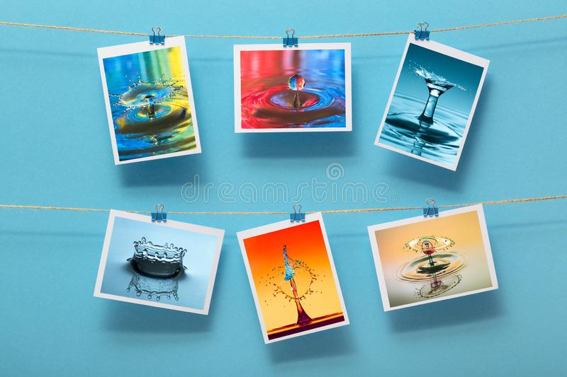Modern art, photo of splash water and paints hanging in rows on a linen thread on stationery clips on a a pastel colored backgroun royalty free stock image