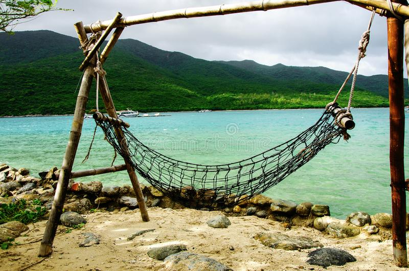 A place of rest and relaxation on the ocean. Hammock on posts on the ocean coast. Close-up. stock photo