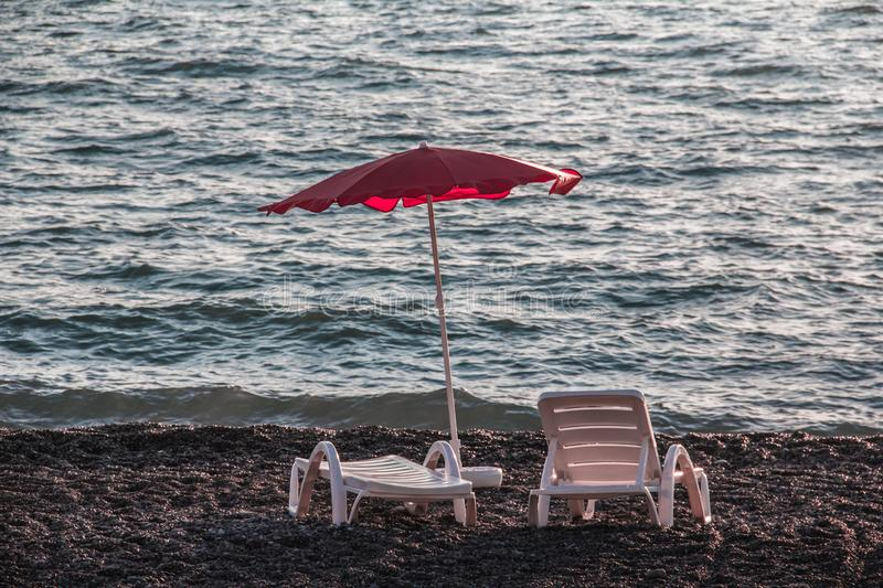 A place by the sea to relax. Sea wave. Black Sea. Beach. Pebble. Element. Sunbeds. Umbrella from the sun royalty free stock photo