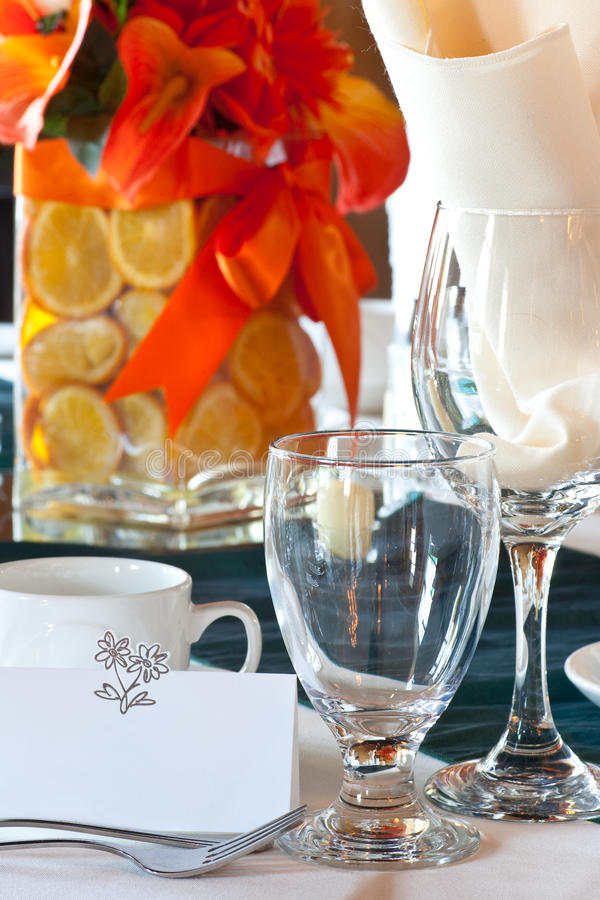 Place setting with center piece & place card. Closeup of a wedding table place setting with colorful centerpiece made up of sliced oranges in a vase with focus stock photos