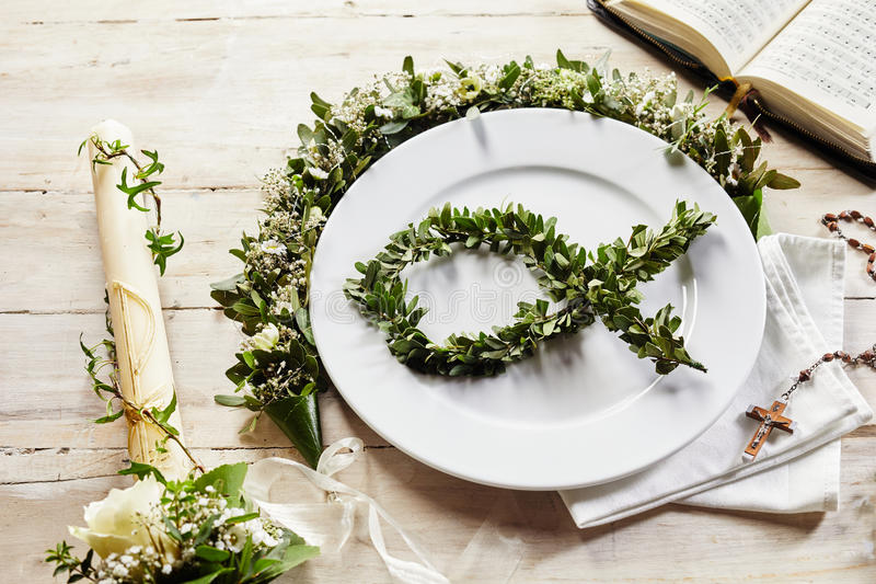 Place setting of christian evening like a christening or holy communion. Decorative dish and cutlery arrangement for invitation of baptism events stock photography