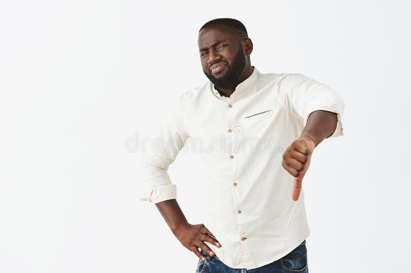 This place sucks, giving my dislike. Portrait of unimpressed displeased gloomy dark-skinned man in white shirt. Grimacing, wrinkling nose and showing thumbs royalty free stock photo