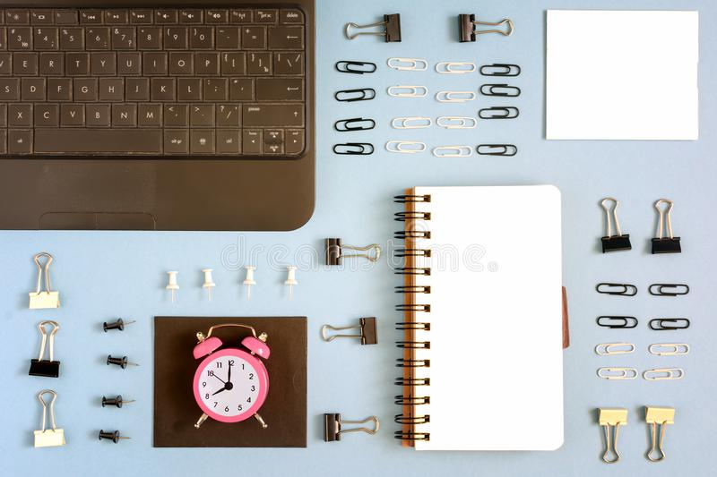 Place for text on a blank page of notepad. Around accurately lay stationery. Small pink alarm clock symbol work time. Concept.Photography top, mock ap stock photography