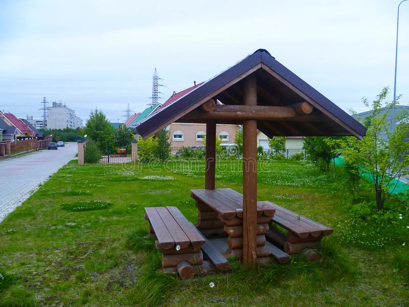 A place to relax in the private sector in gray cloudy summers in the north-west of Russia. Wooden arbor for guests coming to visit royalty free stock images