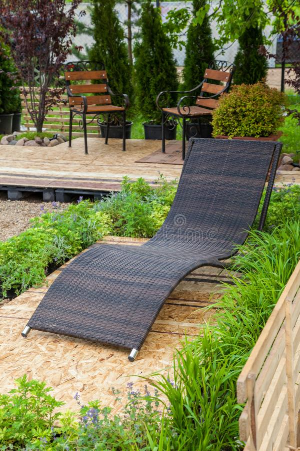A place to relaxation at backyard in garden. A place to relaxation at backyard in garden: lounge chair, wooden chairs, flowerbed and beautiful trees and shrubs stock images