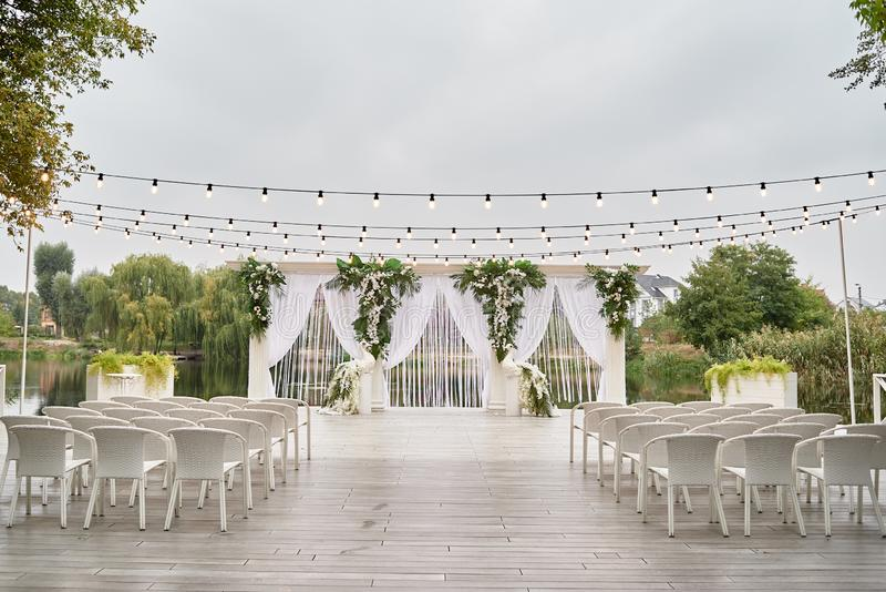 Place for wedding ceremony with wedding arch decorated with palm leaves, orchid flowers and floral peacocks, bulbs garland. White chairs outdoors, copy space royalty free stock photos