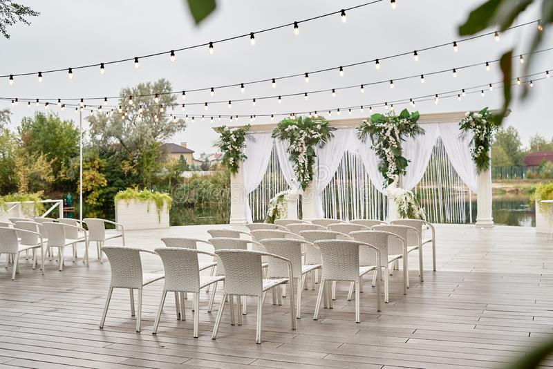 Place for wedding ceremony with wedding arch decorated with palm leaves, orchid flowers and floral peacocks, bulbs garland. White chairs outdoors, copy space stock image