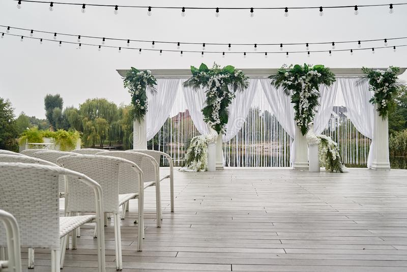 Place for wedding ceremony with wedding arch decorated with palm leaves, orchid flowers and floral peacocks. Place for wedding ceremony with wedding arch royalty free stock photos