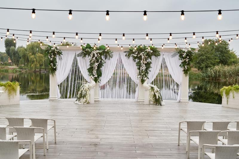 Place for wedding ceremony with wedding arch decorated with palm leaves, orchid flowers and floral peacocks. Place for wedding ceremony with wedding arch stock image