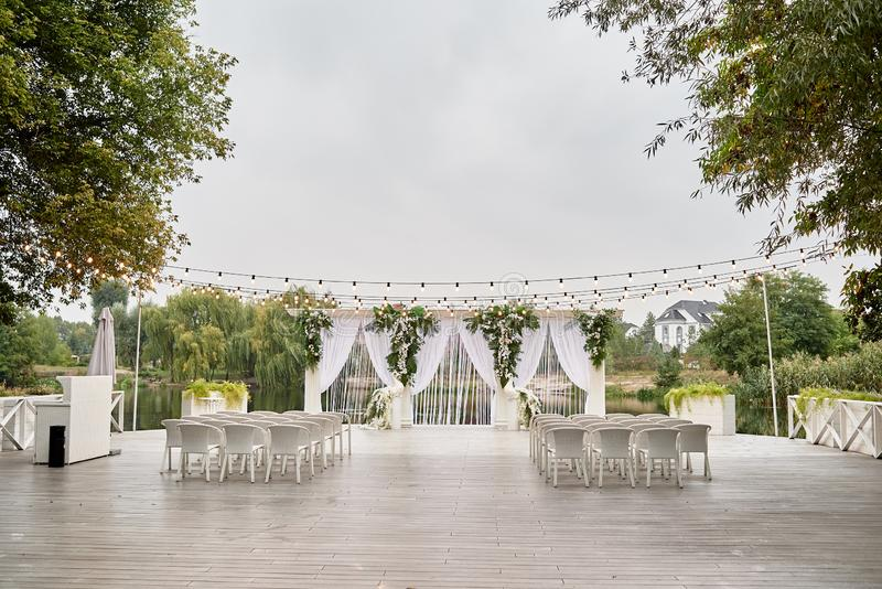 Place for wedding ceremony with wedding arch decorated with palm leaves, orchid flowers and floral peacocks and white chairs. Place for wedding ceremony with stock photo