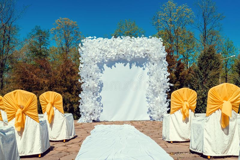 Place for wedding ceremony with white arch and ghairs with yellow cloth outdoors. Empty space for text, copy space. Place for wedding ceremony with white arch stock photo