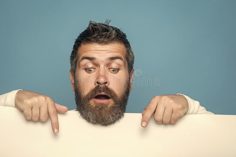 Place for your announcement. Hipster with surprised face hold paper. Feeling and emotions. Man with long beard and mustache. Guy or bearded man on blue stock photography