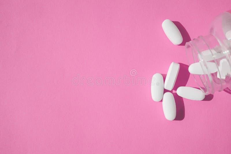 Placebopillen, gefälschte ärztliche Behandlung Schließen Sie herauf weiße Pillen mit Flasche auf Rosa lizenzfreie stockfotos