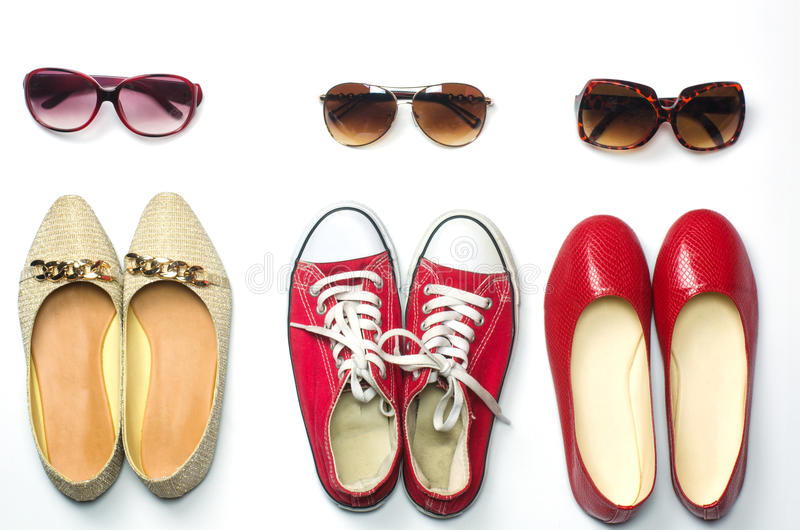 Placed shoes and sunglasses on a white background styles - lifestyles. Placed shoes and sunglasses on a white background styles - lifestyles royalty free stock image