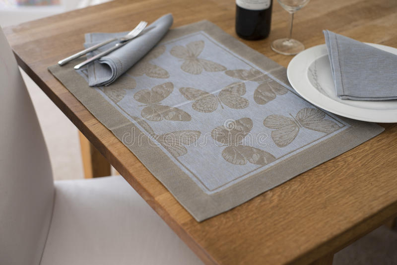 Placemat with Butterfly Design on Table with Napkin on Plate. A rectangular placemat with embroidered butterflies as design spread out on wooden table with royalty free stock images