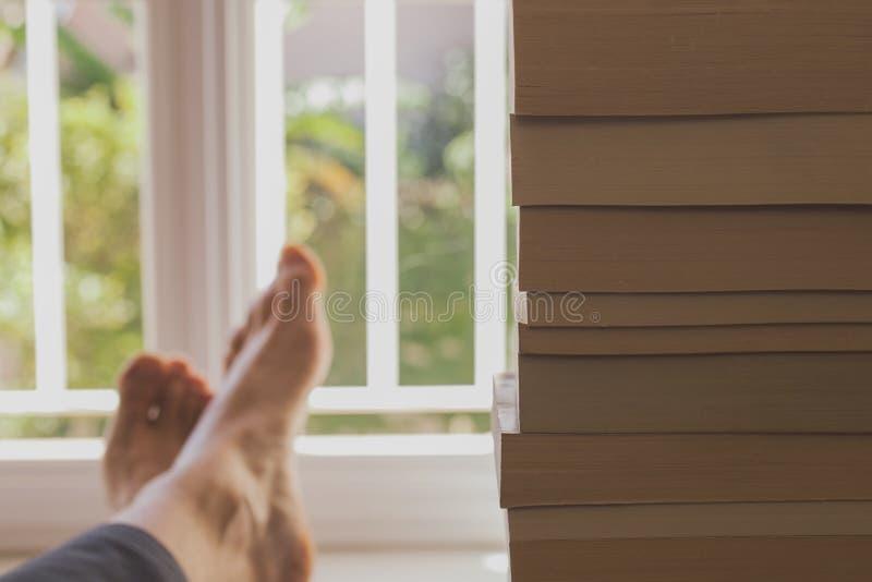 Placer de la lectura Hombre joven que goza de los libros cerca de una ventana fotos de archivo