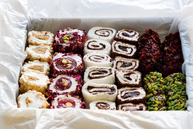 Placer turco con las hojas de las nueces, de los pistachos, del coco, del chocolate y de la rosa en la caja Lokum de Rahat, dulce foto de archivo libre de regalías