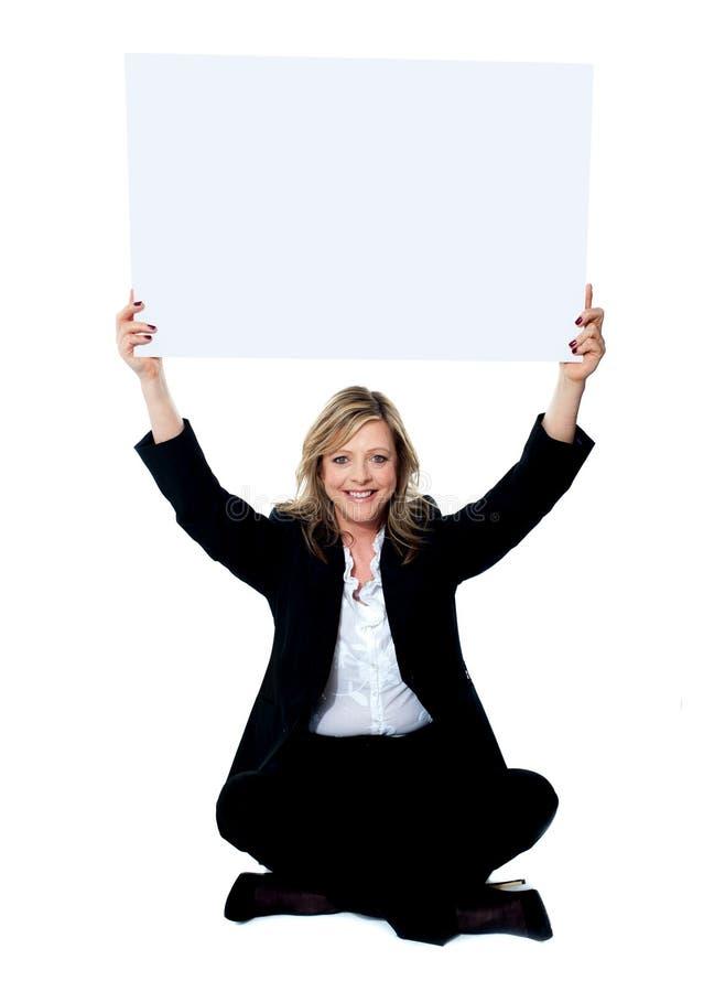 Placerad hållande vit skrivplatta för kvinnlig anställd över hennes huvud royaltyfria bilder