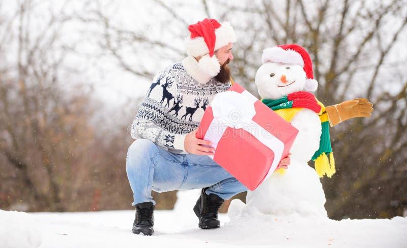 Placering för foto vintersemester varm svettare i kallt väder skäggig man bygga snögubbe Gott nytt år lycklig hipster arkivfoton