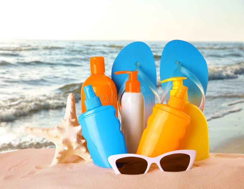 Placez avec différentes bouteilles d'accessoires de crème corporelle et de plage de protection du soleil sur le sable photographie stock libre de droits