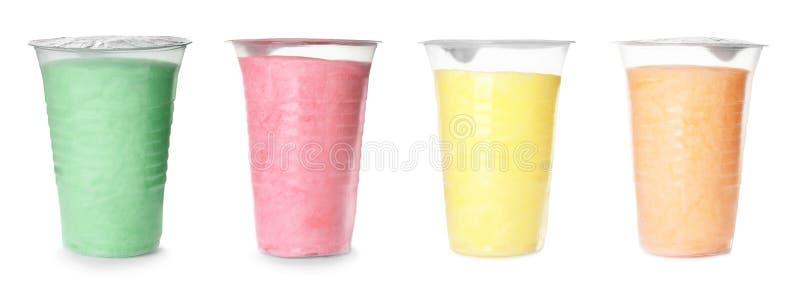 Placez de la sucrerie de coton délicieuse colorée différente dans des tasses en plastique sur le blanc photographie stock libre de droits