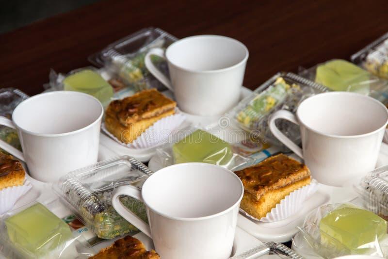 Placez de la tasse et du casse-cro?te sur le plat pour la pause-caf? entre rencontrer le fond clair, concept de caf? photo libre de droits