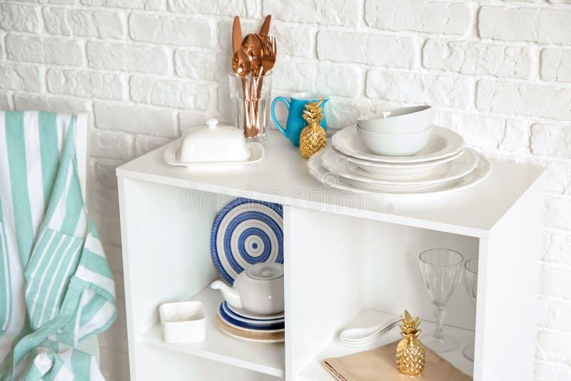Placez de la vaisselle propre sur des étagères près du mur de briques blanc photographie stock libre de droits