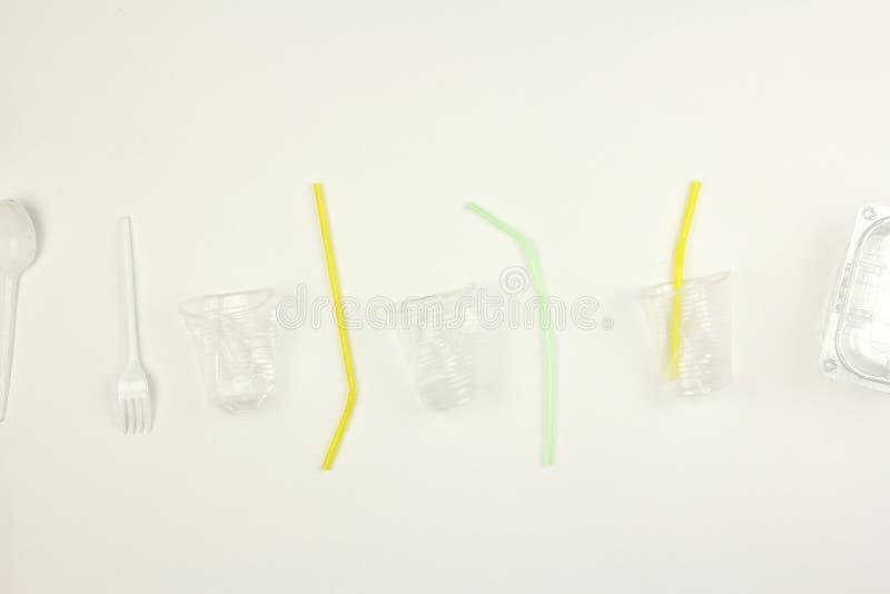 Placez de la vaisselle, de la tasse de cuillère de fourchette et de la paille jetables en plastique utilisées blanches, sur le fo photos libres de droits