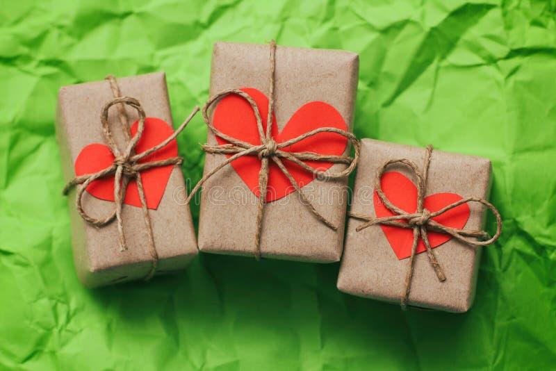 Placez de trois boîte-cadeau attachés avec une corde sur le fond de papier emietté vert Cartes de coeurs de carton images stock