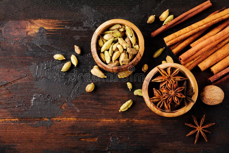Placez des épices de l'anis d'étoile, du cardamome, de la cannelle et du sucre roux sur le vieux fond en bois photographie stock libre de droits