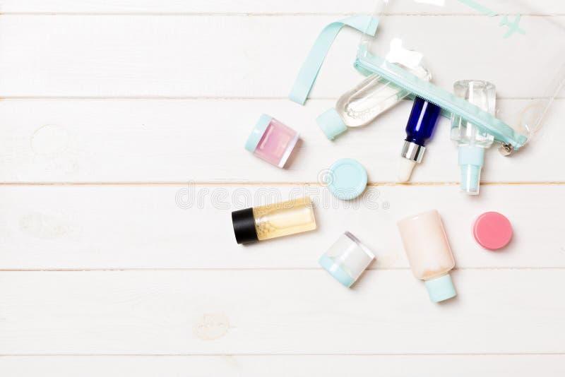 Placez des bouteilles cosmétiques de taille de voyage sur le fond en bois blanc Configuration plate des pots crèmes Vue supérieur photo libre de droits