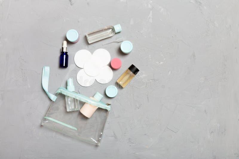 Placez des bouteilles cosmétiques de taille de voyage sur le fond gris Configuration plate des pots crèmes Vue supérieure de conc images stock