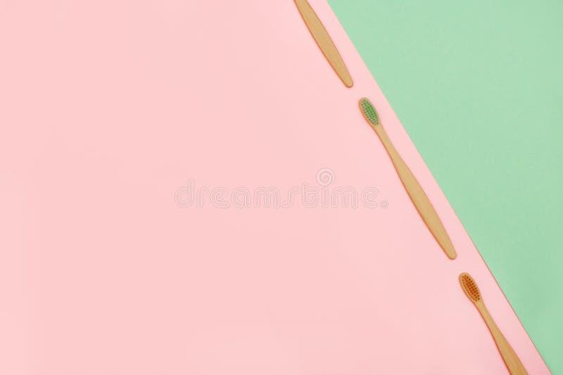 Placez des brosses à dents en bambou dans une rangée sur le rose et le fond de turquoise Vue sup?rieure images stock