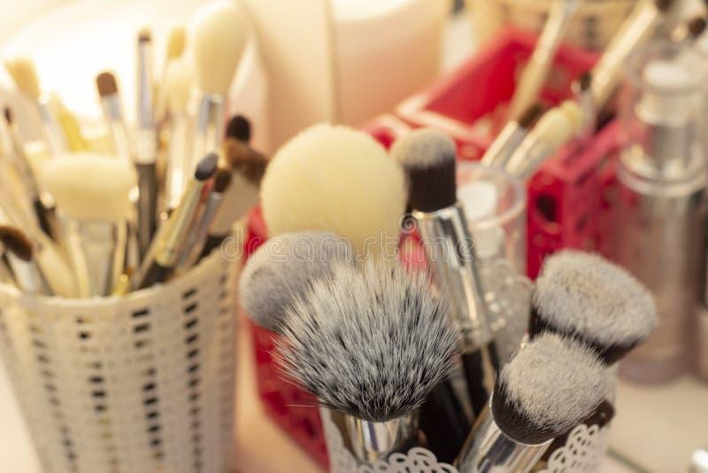 Placez des brosses dans un verre pour appliquer le maquillage maquilleur d'outils et de montages photographie stock