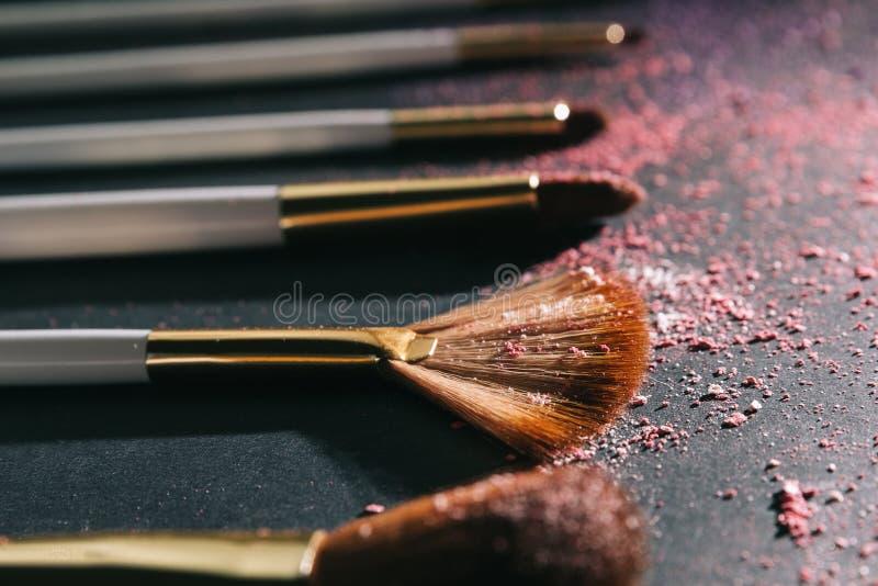 Placez des brosses pour le maquillage professionnel sur un fond noir images libres de droits