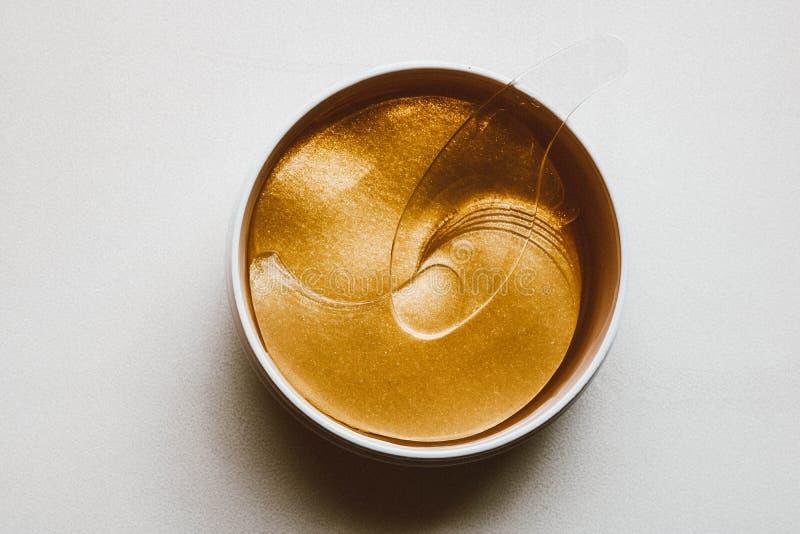 Placez des corrections d'oeil Corrections d'or d'oeil dans le pot en plastique photos libres de droits
