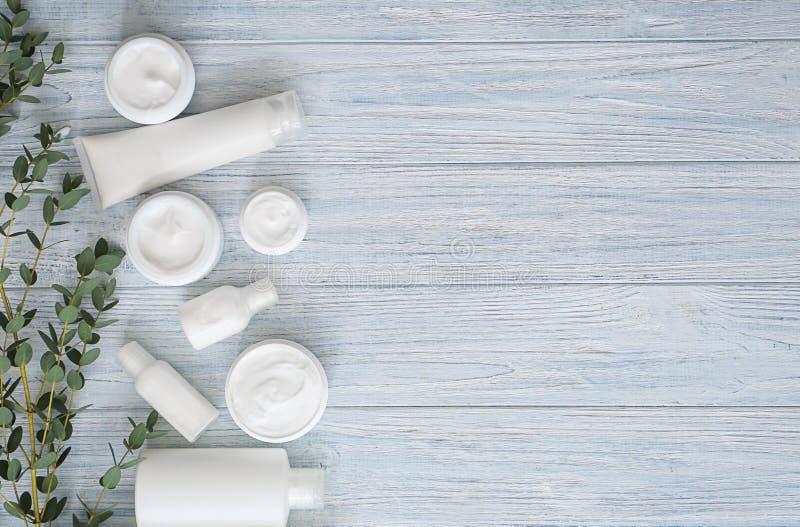 Placez des cosmétiques avec l'extrait de fines herbes sur le fond en bois blanc photo stock