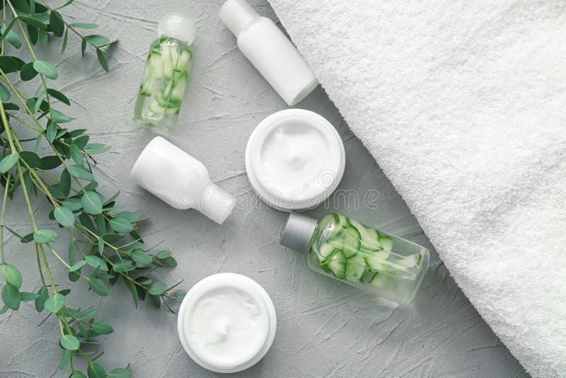 Placez des cosmétiques avec l'extrait de fines herbes sur le fond gris image stock