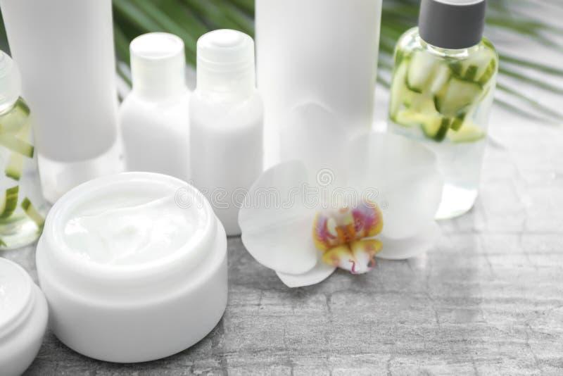 Placez des cosmétiques naturels avec l'extrait de fines herbes sur la table grise photographie stock libre de droits
