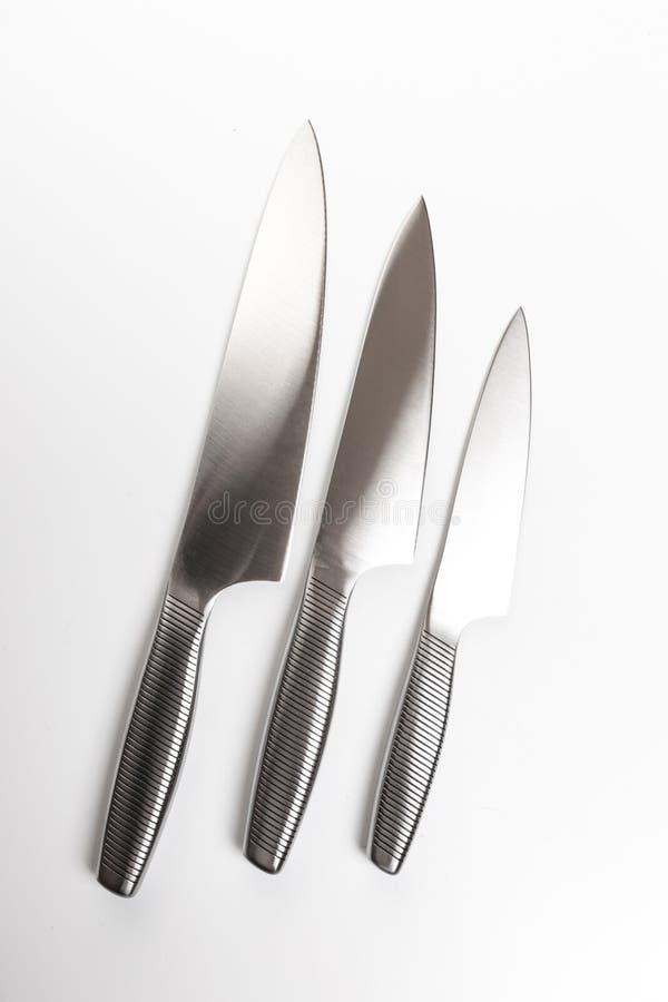 Placez des couteaux de cuisine en acier sur le fond blanc photo libre de droits