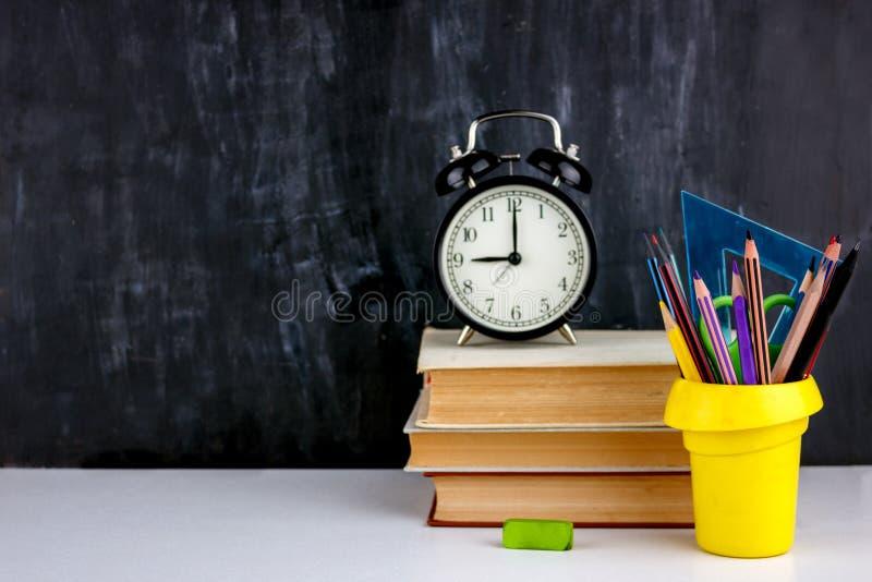 Placez des crayons et des marqueurs colorés pour l'école Papeterie pour l'étudiant - ciseaux, affûteuse, gomme près de la pile de photo stock