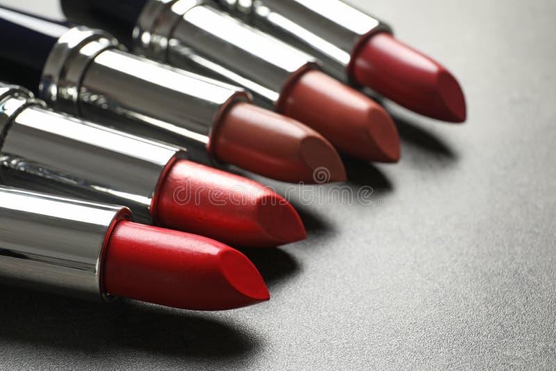 Placez des différents rouges à lèvres sur le fond gris image stock