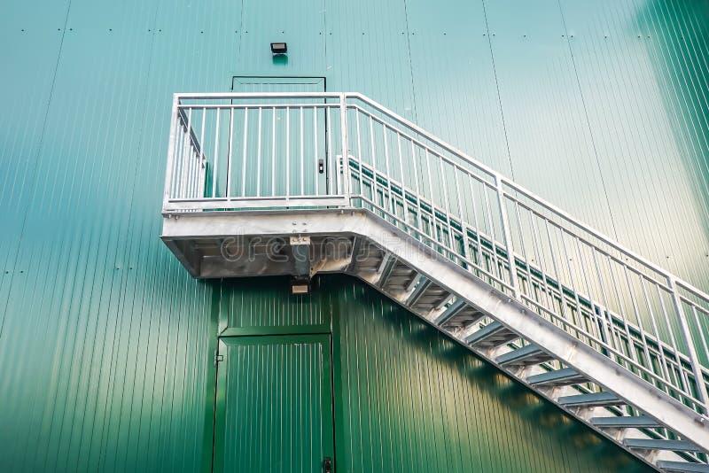 Placez des escaliers et d'une porte dans le mur peint vert dans le côté d'un bâtiment industriel photos libres de droits