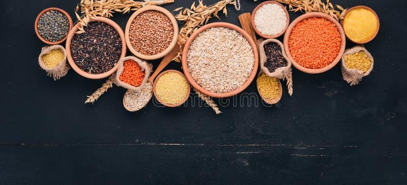 Placez des gruaux et des grains Sarrasin, lentilles, riz, millet, orge, maïs, riz noir Sur un fond noir photos libres de droits